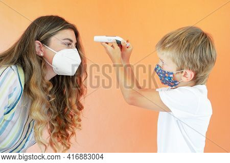 Pandemia Time And Health Concept, Son Measuring Temperature To His Mother With Contactless Temometr,