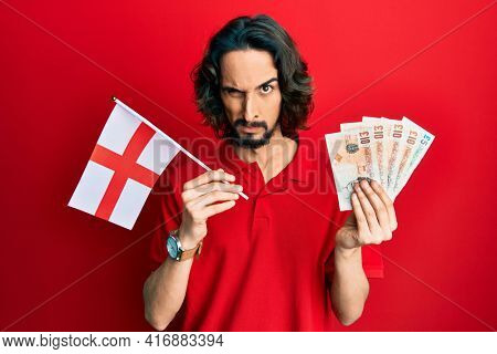Young hispanic man holding england flag and pounds banknotes skeptic and nervous, frowning upset because of problem. negative person.