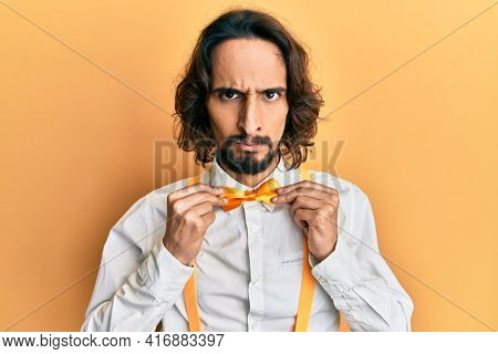 Young hispanic man wearing hipster elegant look holding bowtie skeptic and nervous, frowning upset because of problem. negative person.