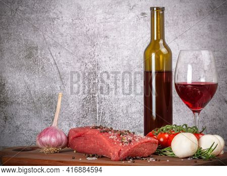 red wine, beef and vegetables on dark wood board