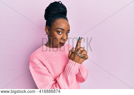 Young african american woman wearing casual winter sweater holding symbolic gun with hand gesture, playing killing shooting weapons, angry face