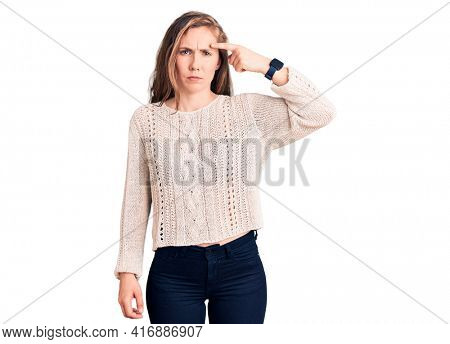 Young beautiful blonde woman wearing casual sweater pointing unhappy to pimple on forehead, ugly infection of blackhead. acne and skin problem