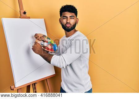 Arab man with beard standing drawing with palette by painter easel stand looking at the camera blowing a kiss being lovely and sexy. love expression.