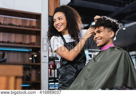 Cheerful African American Hairstylist And Client Looking Away In Salon.