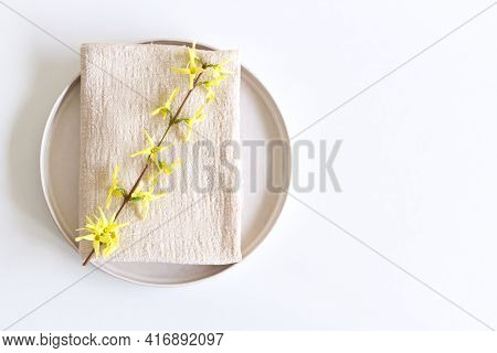 Closeup Of Yellow Blooming Forsythia Flowers, Earthenware Plate And Beige Napkin On White Table Back