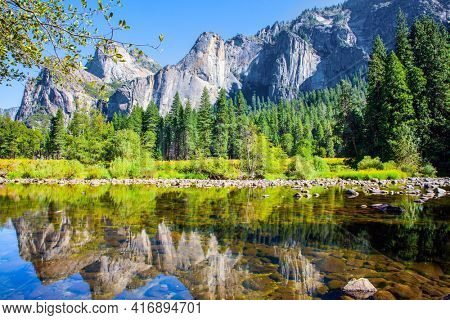 Beautiful day in the park valley. Picturesque El Capitan and mountain peaks are reflected in the smooth water of the Merced River. Yosemite Park is located on the slopes of the Sierra Nevada