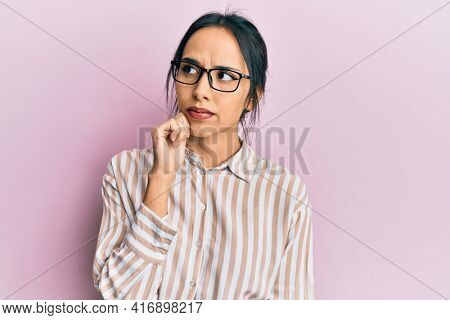 Young hispanic girl wearing casual clothes and glasses thinking concentrated about doubt with finger on chin and looking up wondering