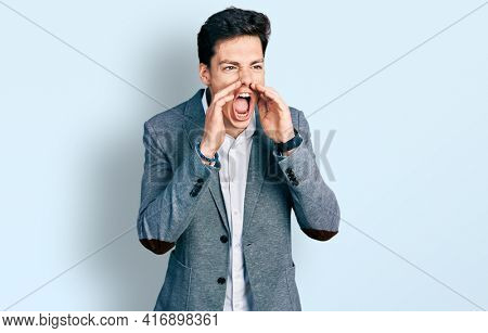 Young hispanic man wearing business clothes shouting angry out loud with hands over mouth