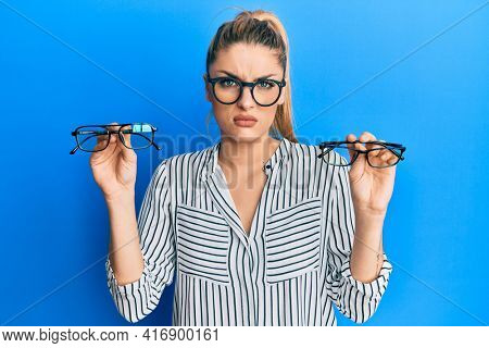 Young caucasian woman holding glasses skeptic and nervous, frowning upset because of problem. negative person.