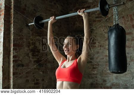 Fitness Woman Performs Barbell Lifting In The Gym. A Woman Lifts A Barbell Over Her Head