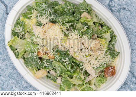 Overhead View Of Caesar Salad Piled High With Cheese, Lettuce, And Dressing To Fill Any Appetite.