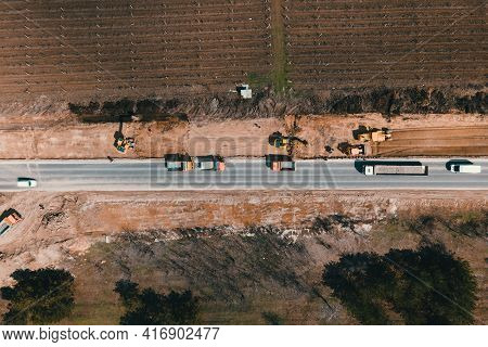 Excavator Digging Ground And Load It Into Dump Truck On Road. Aerial Top Down 4k View Of Special Equ