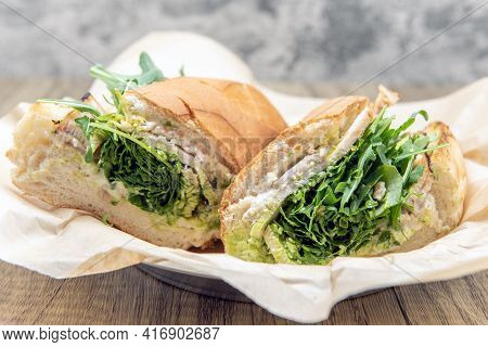 Chicken Sandwich Loaded Inside A Fresh Roll With Arugula, Chicken Breast, Cheese, And Pesto To Fill