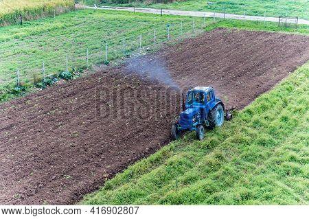 Kaliningrad Region, Russia, September 26, 2020. Fertilizing Fields. Blue Tractor Fertilizing A Field