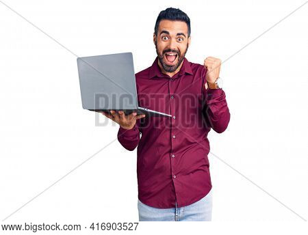 Young hispanic man holding laptop screaming proud, celebrating victory and success very excited with raised arms