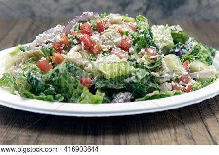 Greek Salad Piled High On A Paper Plate With Romaine Lettuce, Feta Cheese, Cucumber, And Dressing To