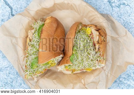 Overhead View Of Fresh Baked Sandwich Roll Loaded With Sandwich Makings Chicken And Sprouts Along Wi