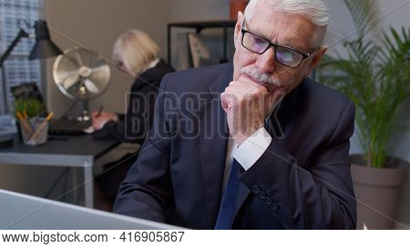Thoughtful Senior Professional Businessman Grandfather Director Working On Laptop Inside Office Pond