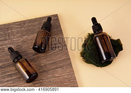 Serum Bottles On Ceramic Tiles With Wood Texture And Pattern On A Beige Background. A Bottle Of Seru