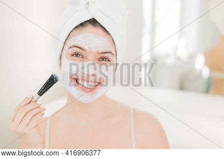 Beautiful Caucasian Woman With A Towel On Her Hair Applies A Clay Face Mask. Taking Care Of Beauty A