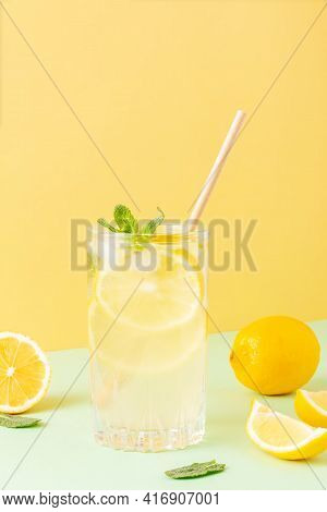 Tall Glass Of Ice Tea Or Water With Ice Cubes, Lemon And Mint Leaves On A Combined Colored Yellow An