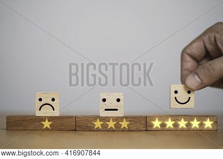 Hand Putting Smiley Face And Golden Yellow Stars Which Print Screen On Wooden Cube Block For Custome
