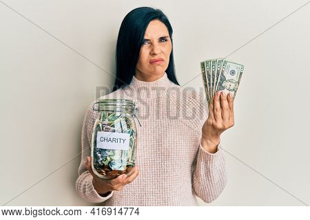 Young caucasian woman holding charity jar and dollars banknotes skeptic and nervous, frowning upset because of problem. negative person.