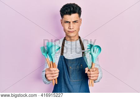 Young hispanic man wearing professional baker apron holding cooking tools skeptic and nervous, frowning upset because of problem. negative person.
