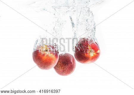 Nectarine Fruits Splashing Into Water And Sinking