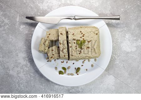 Halva Close Up On A White Plate On A Gray Background. Traditional Oriental Dessert Sweet Halva. Halv