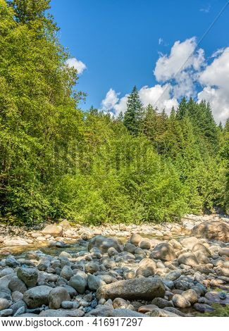Dried Stoney Waterway Of Montailn River On Bright Summer Day