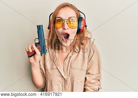 Young caucasian shooter woman using gun scared and amazed with open mouth for surprise, disbelief face