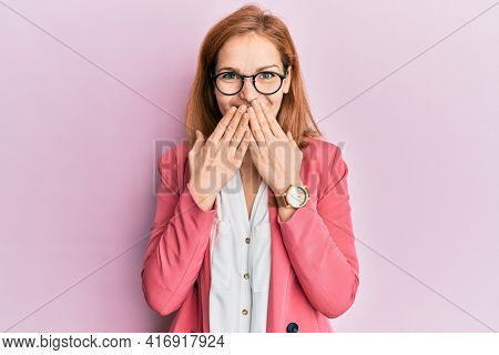 Young caucasian woman wearing business style and glasses laughing and embarrassed giggle covering mouth with hands, gossip and scandal concept
