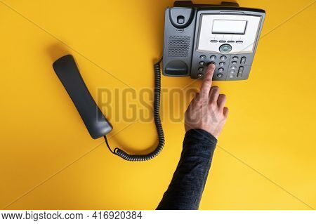 Top View Of A Male Finger Dialing A Telephone Number Using Black Landline Phone. Over Yellow Backgro