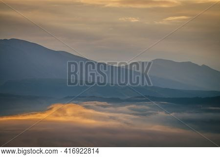 Scenic Dawn Mountain Landscape With Golden Low Clouds In Valley Among Blue Mountains Silhouettes Und