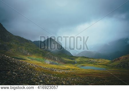 Dramatic Rainy Alpine Landscape With Vivid Low Rainbow In Green Valley Near Rocks And Mountain Lake