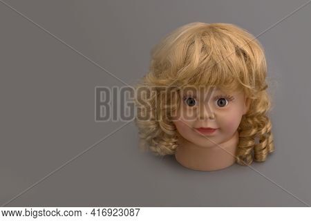 The Head Of A Mannequin Of A Little Girl With Golden Curls On A Gray Background With Copy Sace.shop
