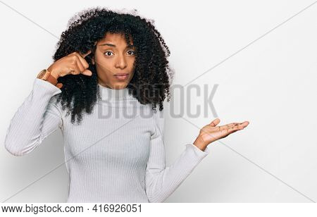 Young african american girl wearing casual clothes confused and annoyed with open palm showing copy space and pointing finger to forehead. think about it.