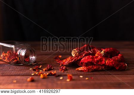 Dried Pepper On A Wooden Background. Cut Pieces Of Pepper Are Poured Out Of A Glass Jar On The Table