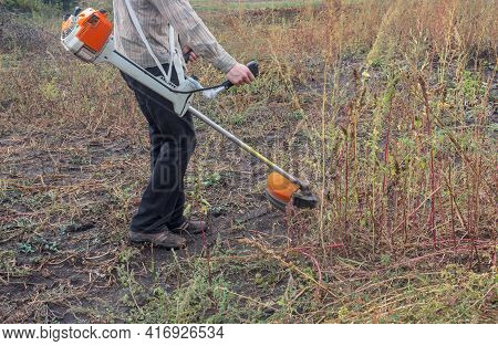 A Worker Cuts Huge Weeds With A Brush Cutter. The Figure Of A Farmer Holding A Trimer. Side View. Cl