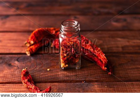 Whole Pieces Of Dried Pepper Lie On A Wooden Table, And Cut Pieces Of It In A Glass Jar Next To It