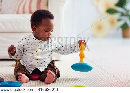Cute Little Baby Boy Playing With Stacking Rings On The Carpet At Home