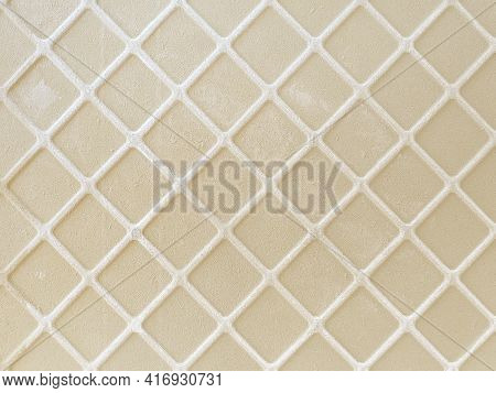 White Rhombuses On Beige Tile. Beige Cement Floor With Rhombus Pattern. Abstract Background And Text