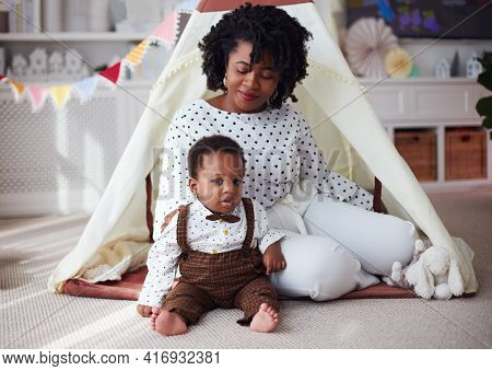 Beautiful Mother With Baby Boy Playing Together On The Carpet In A Nursery Room At Home