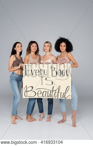 Young Interracial Women Holding Placard With Every Body Is Beautiful Lettering On Grey.