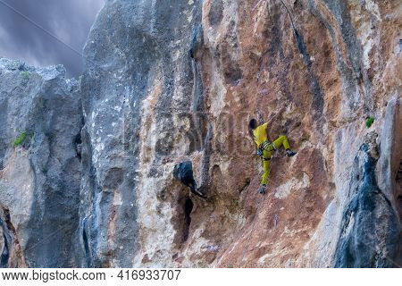A Girl Climbs A Rock On The Background Of The Forest, The Athlete Trains In Nature, Woman Overcomes