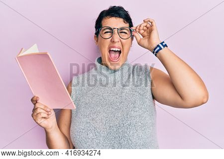 Plus size brunette woman reading a book wearing glasses celebrating crazy and amazed for success with open eyes screaming excited.