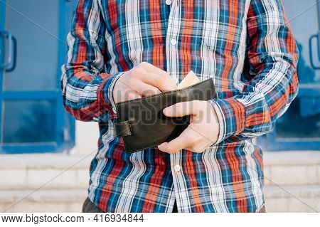 A Man In A Plaid Blue Red Shirt Takes Out A Wallet, Opens It And Looks Inside. The Concept Of Paymen