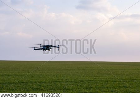 Drone Hovers Over A Green Field Against A Light Sky, Summer Drone Flights, Drone Patrols The Fields.