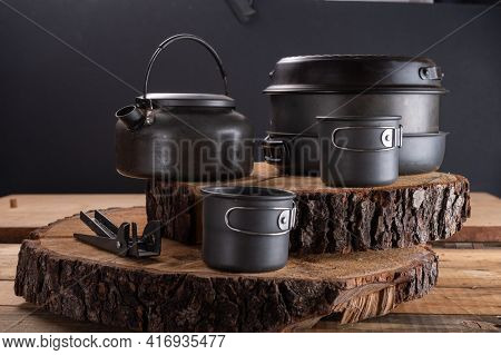 Tourist Utensils Standing On A Wooden Stump. Utensils For Cooking Food On Fire. Front View. Black Ba